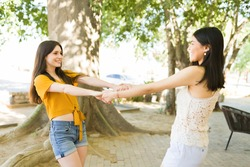Playing like kids at the park. Female best friends in their 20s holding hands and dancing outdoors. Young women twirling at the park