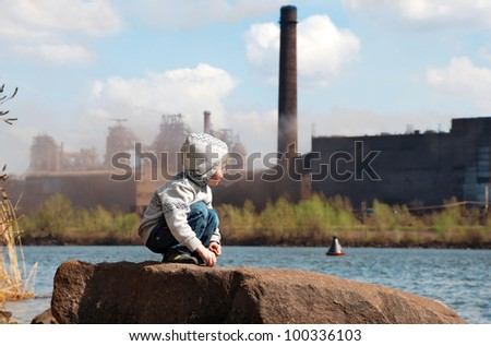 Playing little boy on the river coast in front of metallurgy plant