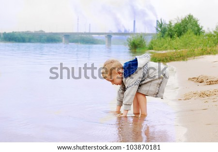 Playing little boy on the river coast near industrial plant