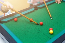Playing mini billiard, pool game on green table, cue, red and yellow balls, two person playing