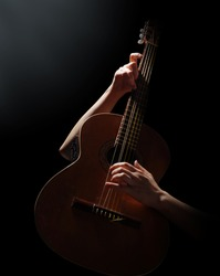 Playing on acoustic guitar on a black background