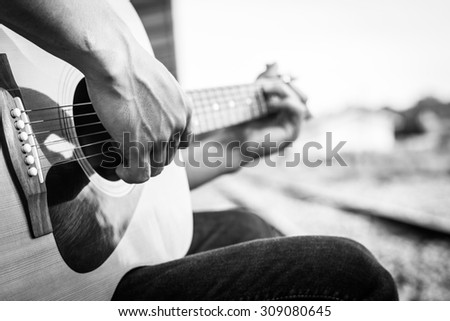 Playing on acoustic guitar outdoor. Black and white photo #309080645