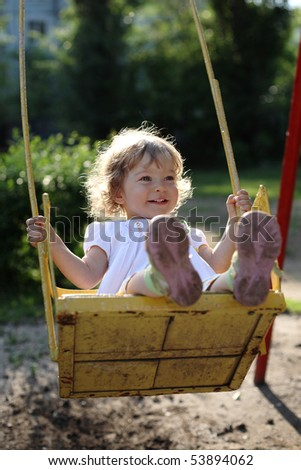 Playing on the swings after summer rain - shallow depth of field, back lighting