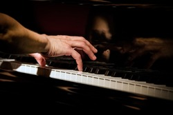 Playing piano at concert, focus on right hand, close up at low light conditions