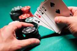 Playing poker in the casino. Cards with two pairs in the hand of the player making a bet with chips on a green table background