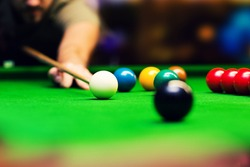 playing snooker - man aiming the cue ball