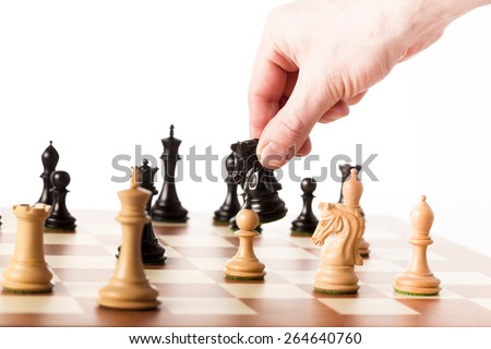 Playing the chess game - a hand moving the black knight - making strategic decisions