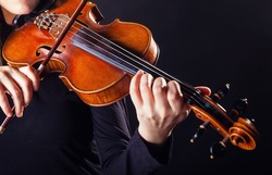 Playing the violin. Musical instrument with performer hands on dark background