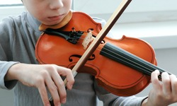 Playing the violin. Unrecognizable seven years old boy playing the violin closeup. Front view.