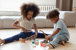 Playing together. Focused attentive black african children younger brother and elder sister, two little cousins friends enjoying interesting game with toys and bricks on warm floor at home in playroom