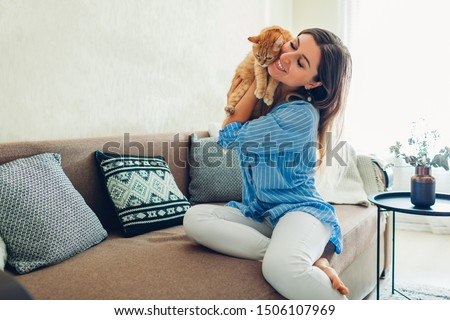 Playing with cat at home. Young woman sitting on couch and hugging pet. ストックフォト ©