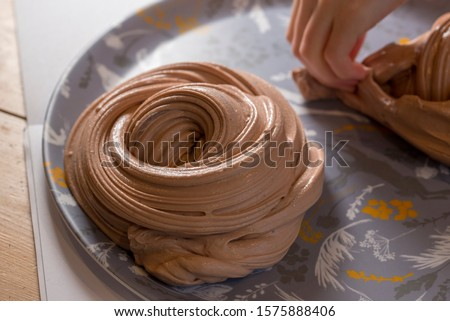 Playing with creamy chocolate brown slime making swirls and stretching it out #1575888406