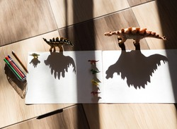 Playing with light and shadow. Outline the shadow of the toy dinosaur figure. Childhood, games for the development of children's creativity at home