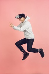 Playing with VR-headset. Caucasian young man's modern portrait isolated on pink studio background. Beautiful male model in high jump. Concept of human emotions, facial expression, sales, ad. Copyspace