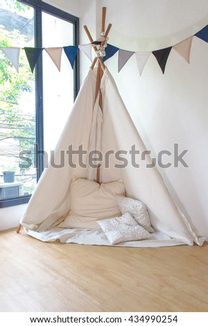 Playroom for kids with Teepee or DIY tent, decorated flags. Window Lights. Soft Focus. Slightly grained filter.