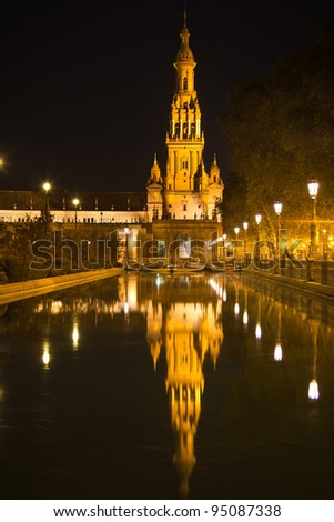 Plaza de Espana in Sevilla at night, Spain. Tower reflected in the canal. Built in 1928 for the Ibero-American Exposition of 1929. It is a landmark example of the Renaissance Revival style