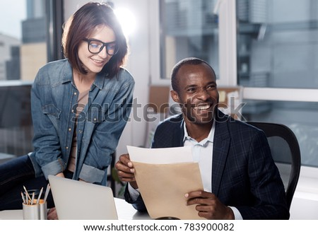 Pleasant atmosphere. Optimistic skillful team is working in office. Cheerful man is sitting at desk and holding documents while looking aside with wide smile. Young woman is leaning over table