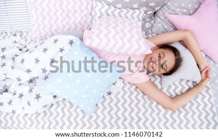 Pleasant awakening. Girl smiling happy child lay on bed with star pattern pillows and cute plaid in her bedroom. Bedclothes for children. Modern fashionable bedclothes. Girl kid waking up in morning.