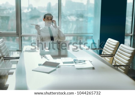 Pleasant chat. Upbeat young worker sitting at the empty table in the conference room and chatting happily with someone on the phone during the break from work