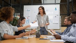Pleasant confident millennial female boss giving out paper document report to motivated african american employee, while mixed race business people group looking through project results at meeting.