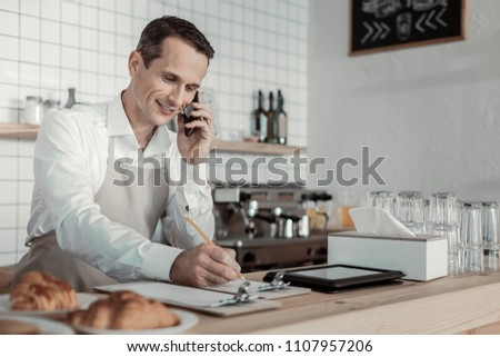 Pleasant conversation. Cheerful man keeping smile on his face while looking at his notes