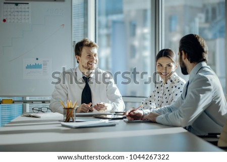 Pleasant conversation. Upbeat young colleagues sitting at the table during the meeting and chatting cheerfully with each other while smiling