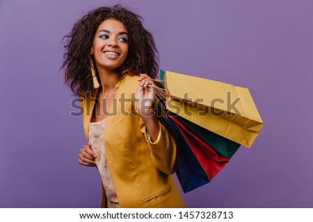 Pleasant curly woman enjoying shopping. Amazing brunette girl posing in yellow jacket.