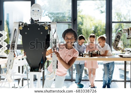 Pleasant girl looking out from behind a human robot #683338726