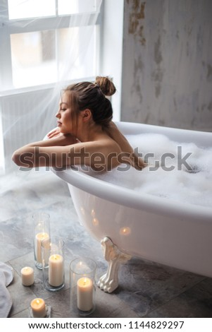 pleasant girl pampering her body in the spa salon with candles on the floor #1144829297