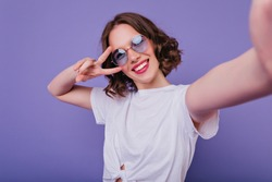 Pleasant girl with tattoo making selfie in studio and laughing. Good-looking young woman with brown wavy hair taking picture of herself on bright purple background.