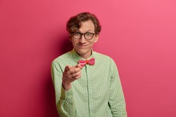 Pleasant looking cheerful European male nerd indicates at camera, has funny look, smiles broadly, wears shirt and spectacles, chooses you, isolated on pink studio wall. People, choice concept