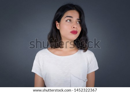 Pleasant looking young female student, looks pensively aside, plans actions after university, imagines what to do. Clever woman thinks over about new project. Copy space on gray.