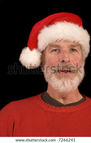 Pleasant middle-aged bearded man in a santa hat and red sweater over a black background