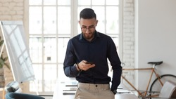 Pleasant millennial arabic businessman using smartphone at modern workplace. Successful young arabian employee in eyeglasses texting message, checking corporate email, using mobile applications.