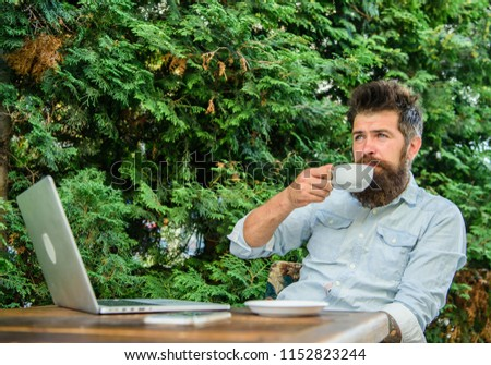 Pleasant moment. Take moment to enjoy life. Man bearded hipster make pause for drink coffee and relax while sit with laptop. Guy drinks coffee relaxing terrace branches background. Aroma cappuccino. #1152823244