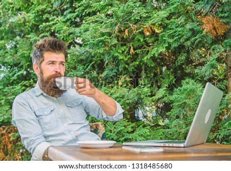 Pleasant moment. Take moment to enjoy life. Man bearded hipster make pause for drink coffee and relax while sit with laptop. Guy drinks coffee relaxing terrace branches background. Aroma cappuccino. #1318485680