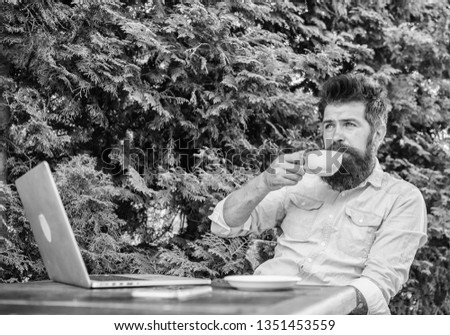 Pleasant moment. Take moment to enjoy life. Man bearded hipster make pause for drink coffee and relax while sit with laptop. Guy drinks coffee relaxing terrace branches background. Aroma cappuccino. #1351453559