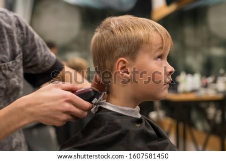 Pleasant professional barber using haircutting machine