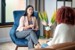 Pleasant psychoanalyst. Stylish pleasant psychoanalyst wearing nice jacket talking to her client