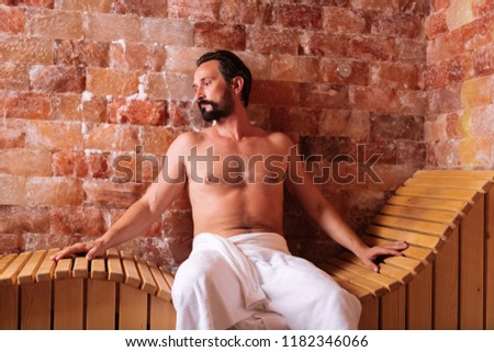 Pleasant relaxation. Handsome bearded man sitting on the wooden bench while relaxing in the spa #1182346066