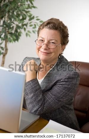Pleasant senior executive woman at her desk