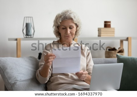 Pleasant smiling elderly mature woman sitting on sofa, holding laptop on lap, reading banking loan paper notification. Happy older senior grandmother looking through mail letter alone at home.