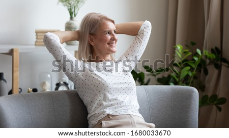 Pleasant smiling middle aged woman relaxing on cozy coach in modern living room, looking away. Happy older lady dreaming, visualizing future, resting, enjoying weekend free leisure time alone at home. Photo stock ©