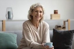 Pleasant smiling middle aged woman sitting on sofa with cup of hot tea, looking at camera. Happy attractive older mature lady enjoying free leisure weekend morning time with coffee alone at home.