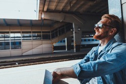Pleasant smiling young man sitting while resting on the railway station and waiting for a tain