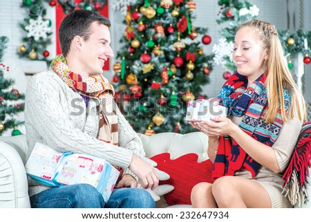 Pleasant surprise. Man gives his wife a Christmas present. Young couple in love man and pretty girl wearing sweater and scarf at home