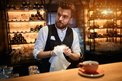 pleasant thoughtful barista cleaning glasses, holding glass and cloth, working at bar, coffee shop.job, profession, occupation. happy handosme waiter in elegant suit working at the table