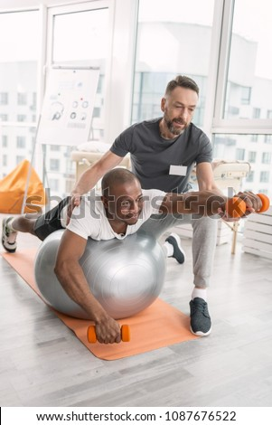 Pleasant workout. Joyful nice positive man smiling while enjoying the physical training