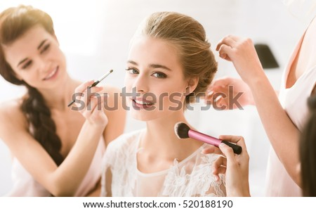 Pleasant young bridesmaids helping the bride to get ready