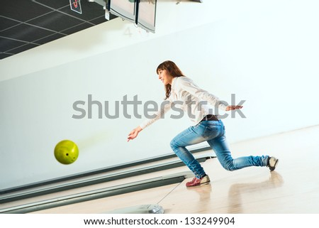 pleasant young woman throws a bowling ball, looks at the target and smiling